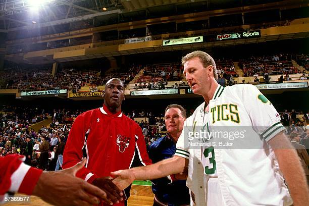 Larry Bird of the Boston Celtics shakes hands with Michael Jordan of the Chicago Bulls prior to a game circa 1991 at the Boston Garden in Boston...