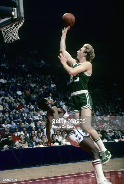 Larry Bird of the Boston Celtics shoot a short one handed jump shot over a Washington Bullets defender during a circa 1980 NBA basketball game at the...