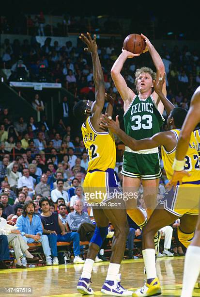 Larry Bird of the Boston Celtics shoot over James Worthy and Magic Johnson of the Los Angeles Lakers during an NBA basketball game circa 1985 at The...