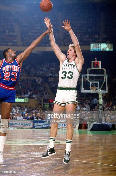 Larry Bird of the Boston Celtics shoots a jump shot against Earl Cureton of the Detroit Pistons during a game played in 1985 at the Boston Garden in...