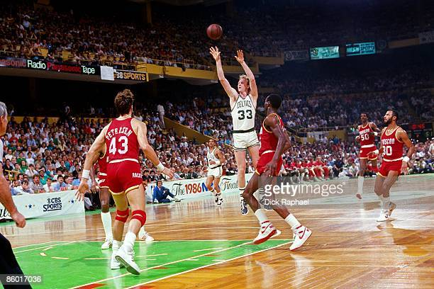 Larry Bird of the Boston Celtics shoots a jump shot against the Houston Rockets during an NBA game played in 1986 at the Boston Garden in Boston...
