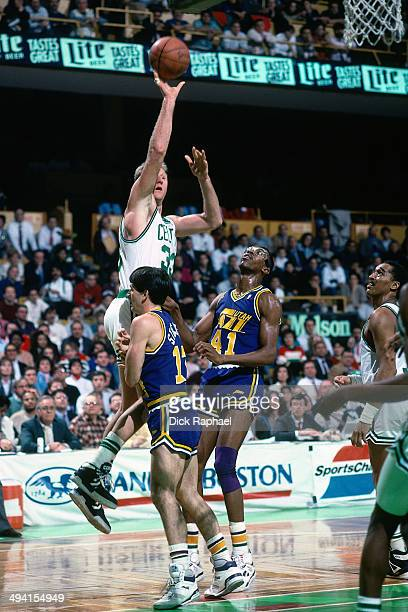 Larry Bird of the Boston Celtics shoots against Thurl Bailey and John Stockton of the Utah Jazz during a game played circa 1990 at the Boston Garden...