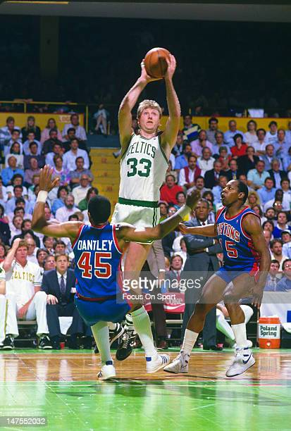 Larry Bird of the Boston Celtics shoots over Adrian Dantley and Vinnie Johnson of the Detroit Pistons during an NBA basketball game circa 1987 at The...