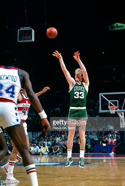 Larry Bird of the Boston Celtics shoots over Greg Ballard of the Washington Bullets during an NBA basketball game circa 1983 at the Capital Center in...