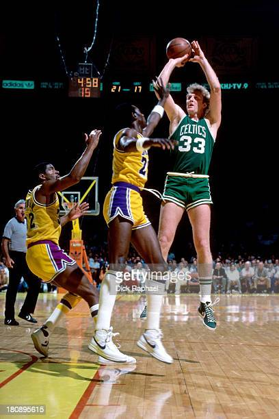 Larry Bird of the Boston Celtics shoots over Michael Cooper of the Los Angeles Lakers during a game circa 1984 at the Boston Garden in Boston...