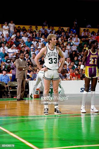 Larry Bird of the Boston Celtics stands next to Michael Cooper of the Los Angeles Lakers during Game Six of the 1985 NBA Finals played on June 9 at...