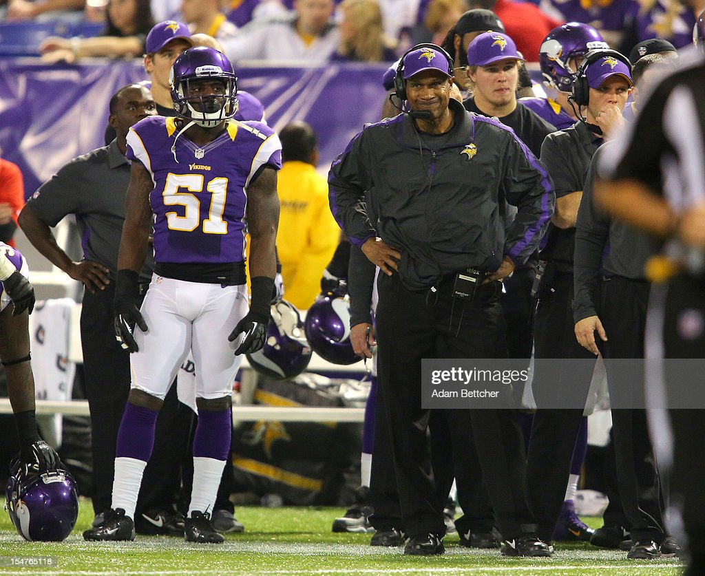 Larry Dean #51 (L) and head coach Leslie Frazier of the Minnesota Vikings watch from the sidelines against the Tampa Bay Buccaneers at the Hubert H. Humphrey Metrodome on October 25, 2012 in Minneapolis, Minnesota.