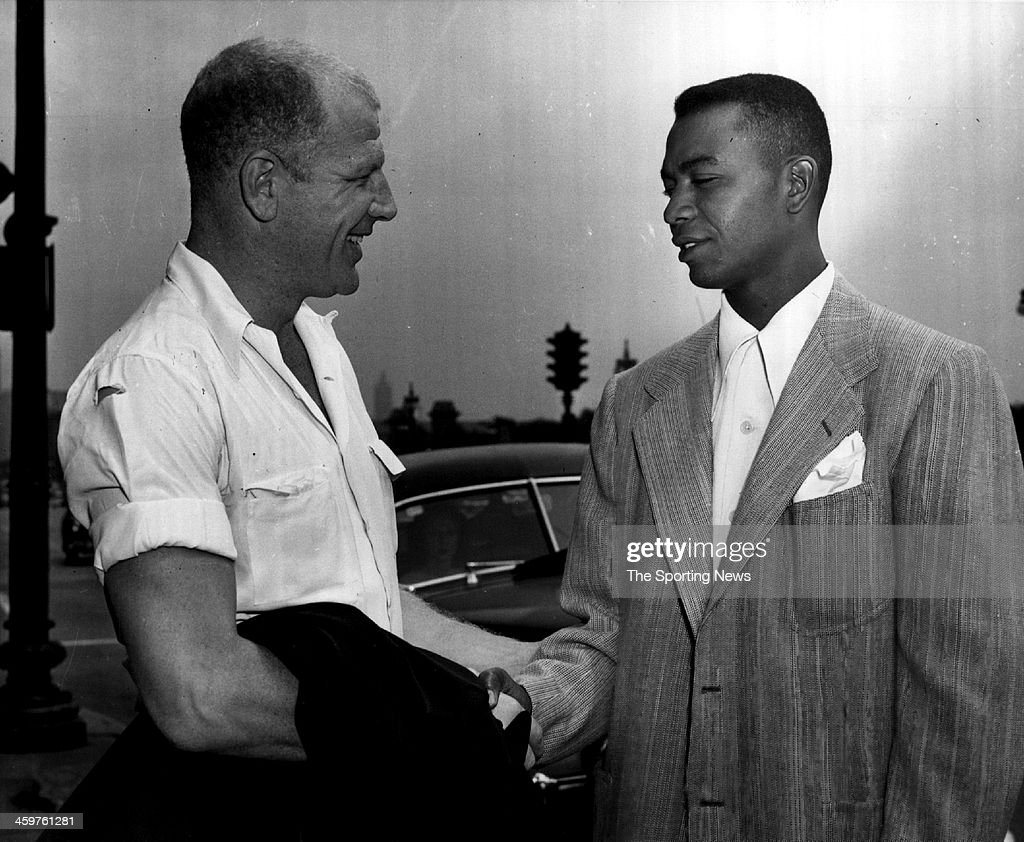 Larry Doby (right), the American league's first black player, shakes hands with his new boss, President Bill Veeck of the Cleveland Indians', after Doby arrived in Chicago, IL on July 5, 1948 from Newmark, N.J. to join the Cleveland club.