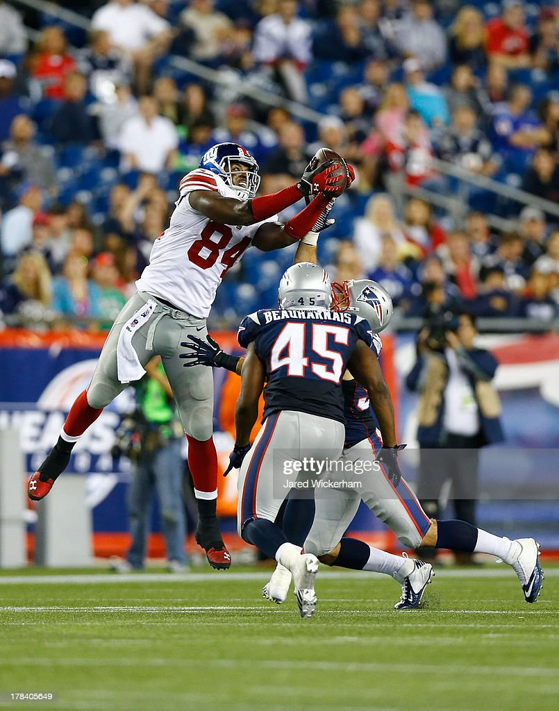 Larry Donnell #84 of the New York Giants catches a deflected pass in the fourth quarter in front of Steve Beauharnais #45 of the New England Patriots during the preseason game at Gillette Stadium on August 29, 2013 in Foxboro, Massachusetts.