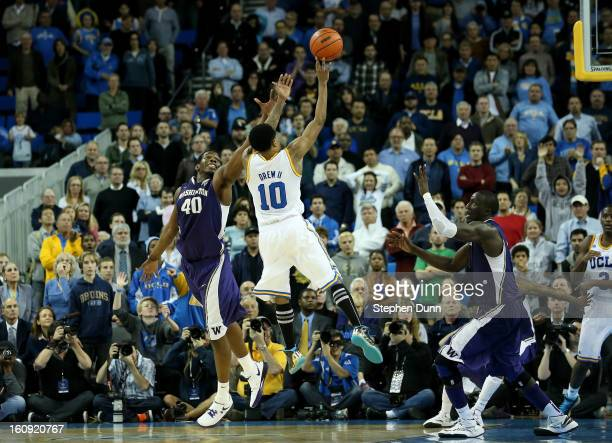 Larry Drew II of the UCLA Bruins makes the winning basket as time runs out in the game against Sean Kemp Jr#40 and Aziz N'diaye of the Washington...
