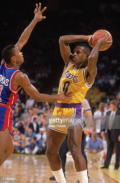 Larry Drew of the Los Angeles Lakers passes over Isiah Thomas of the Detroit Pistons during an NBA game at the Great Western Forum in Los Angeles...
