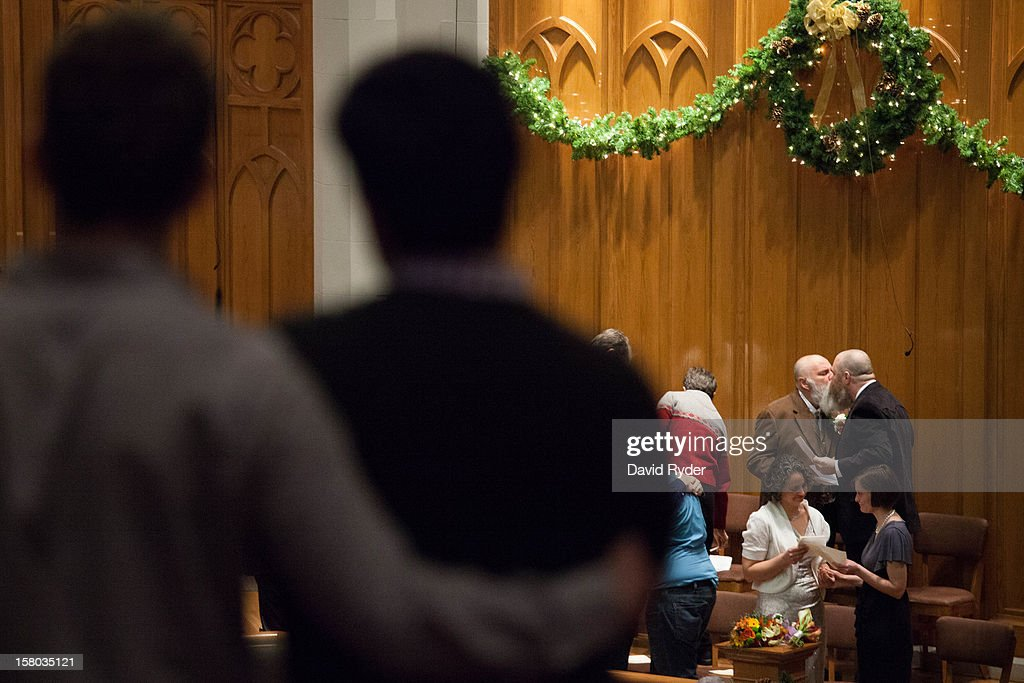 Larry Duncan and Randy Shepherd (far right) kiss at the end of a mass wedding for 25 couples at Seattle First Baptist Church on December 9, 2012 in Seattle, Washington. Today is the first day that same-sex couples can legally wed in Washington state.