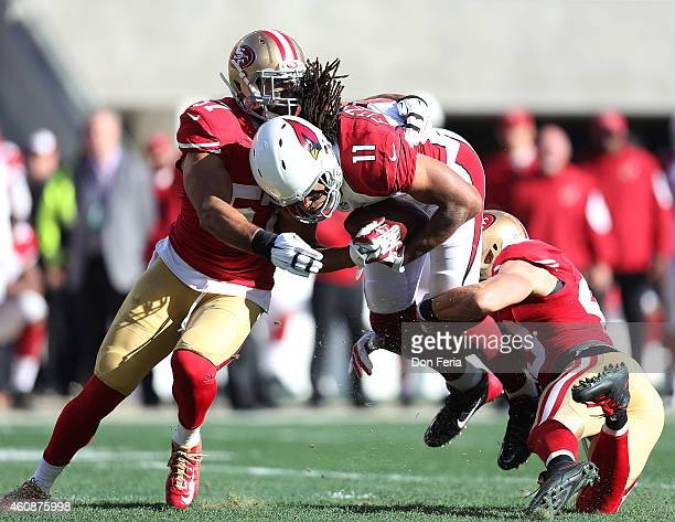 Larry Fitzgerald of the Arizona Cardinals is stopped by Michael Wilhoite of the San Francisco 49ers and Craig Dahl of the San Francisco 49ers in the...