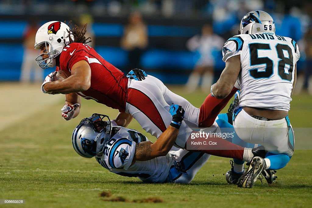 Larry Fitzgerald of the Arizona Cardinals is tackled by Kurt Coleman of the Carolina Panthers in the first half during the NFC Championship Game at...