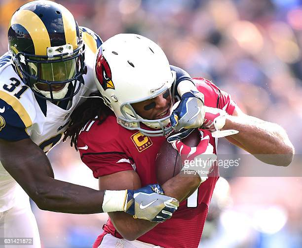 Larry Fitzgerald of the Arizona Cardinals is tackled by Maurice Alexander of the Los Angeles Rams after his catch at Los Angeles Memorial Coliseum on...