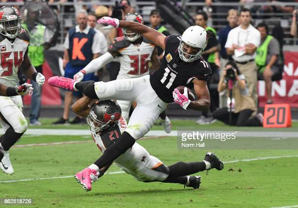 Larry Fitzgerald of the Arizona Cardinals jumps over a tackle by Justin Evans of the Tampa Bay Buccaneers during the second quarter at University of...