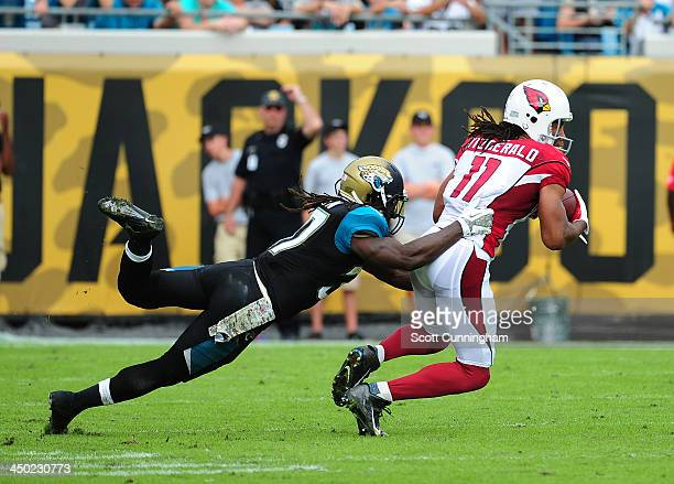Larry Fitzgerald of the Arizona Cardinals runs with a catch against Johnathan Cyprien of the Jacksonville Jaguars at EverBank Field on November 17...