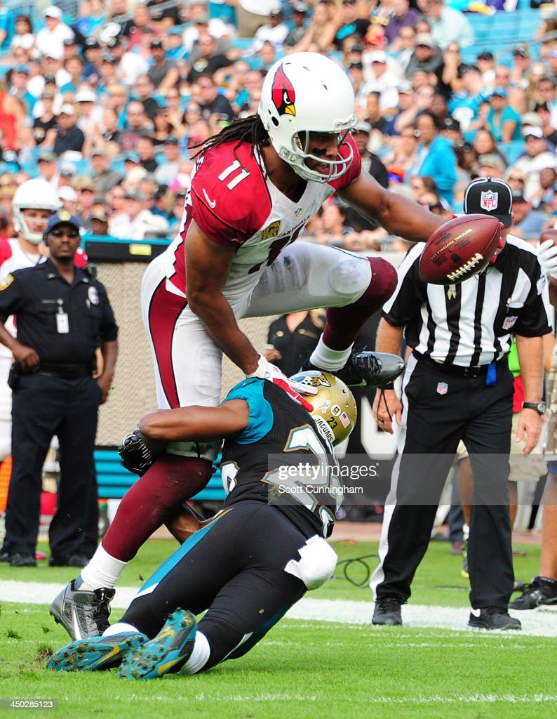 Larry Fitzgerald #11 of the Arizona Cardinals runs with a catch against Alan Ball #23 of the Jacksonville Jaguars at EverBank Field on November 17, 2013 in Jacksonville, Florida.