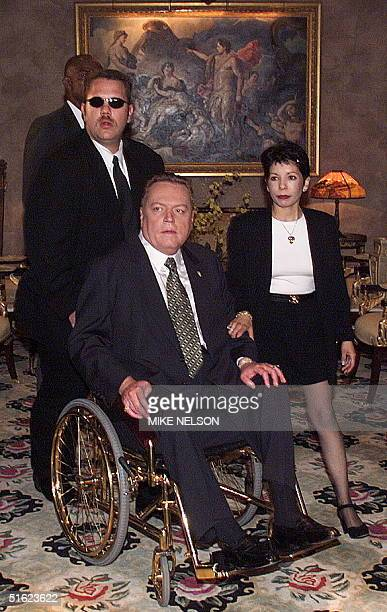 Larry Flynt publisher of Hustler magazine is wheeled by his bodyguard and accompanied by his assistant prior to a press conference 11 January in...
