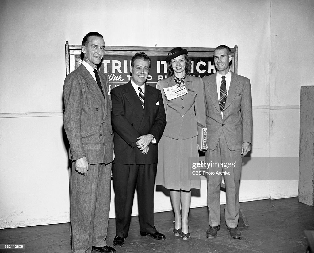 Larry Harding, assistant director of CBS Radio quiz and game show, 'Strike It Rich' is pictured with program host Todd Russell and contestants Mrs. and Mr. Crom from Brooklyn NY. December 23, 1947 New York, NY.