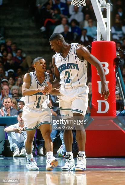 Larry Johnson and Muggsy Bogues of the Charlotte Hornets celebrate after a play during an NBA basketball game circa 1993 at the Charlotte Coliseum in...