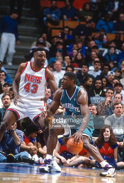 Larry Johnson of the Charlotte Hornets backs in on Armen Gilliam of the New Jersey Nets during an NBA basketball game circa 1993 at the Brendan Byrne...