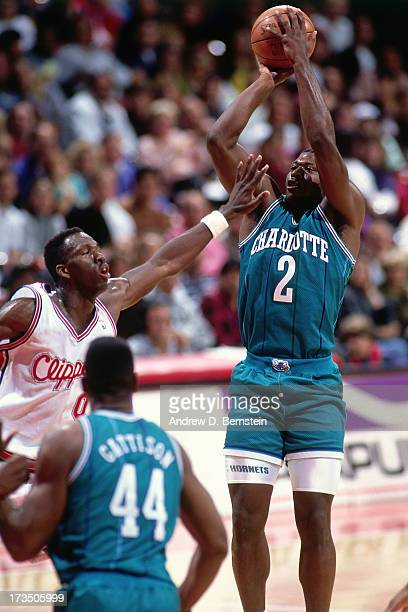 Larry Johnson of the Charlotte Hornets shoots against Olden Polynice of the Los Angeles Clippers during a game played circa 1991 at the Los Angeles...