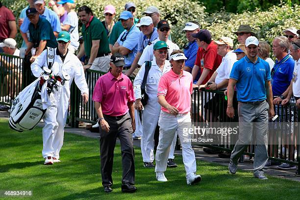 Larry Mize of the United States Bernhard Langer of Germany and Martin Kaymer of Germany walk together during the Par 3 Contest prior to the start of...