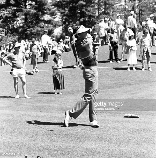 Larry Mize watches his shot from the finish position in front of a small gallery during the 1988 Masters Tournament at Augusta National Golf Club in...