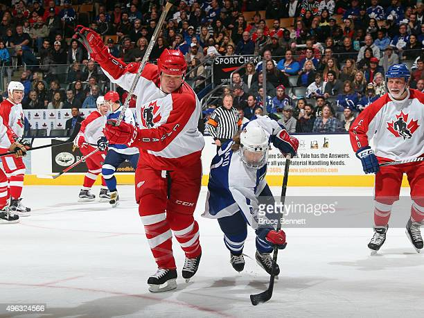Larry Murphy bumps Cammi Granato during the first period at the Legends Classic game at the Air Canada Centre on November 8 2015 in Toronto Ontario...