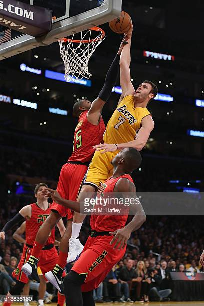 Larry Nance Jr #7 of the Los Angeles Lakers dunks over Al Horford and Paul Millsap of the Atlanta Hawks during the first half of a game at Staples...