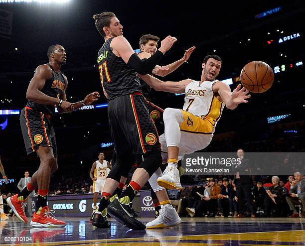 Larry Nance Jr #7 of the Los Angeles Lakers falls backwards as he is defended by Mike Muscala Kyle Korver and Dwight Howard of the Atlanta Hawks...