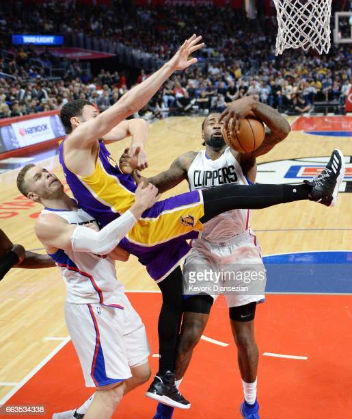 Larry Nance Jr #7 of the Los Angeles Lakers is tackled by Blake Griffin of the Los Angeles Clippers as DeAndre Jordan of the Los Angeles Clippers...