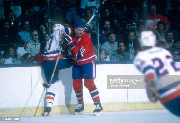 Larry Robinson of the Montreal Canadiens checks John Tonelli of the New York Islanders into the boards during an NHL game on March 4 1986 at the...