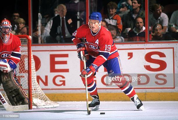 Larry Robinson of the Montreal Canadiens skates with the puck as goalie Patrick Roy looks on during an NHL game circa 1988 at the Spectrum in...