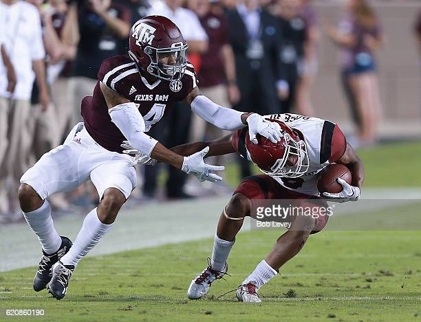 Larry Rose III of the New Mexico State Aggies attempts to break the tackle attempt by Justin Evans of the Texas AM Aggies at Kyle Field on October 29...