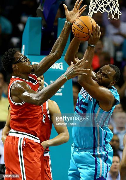 Larry Sanders of the Milwaukee Bucks and Al Jefferson of the Charlotte Hornets go after a rebound during their game at Time Warner Cable Arena on...