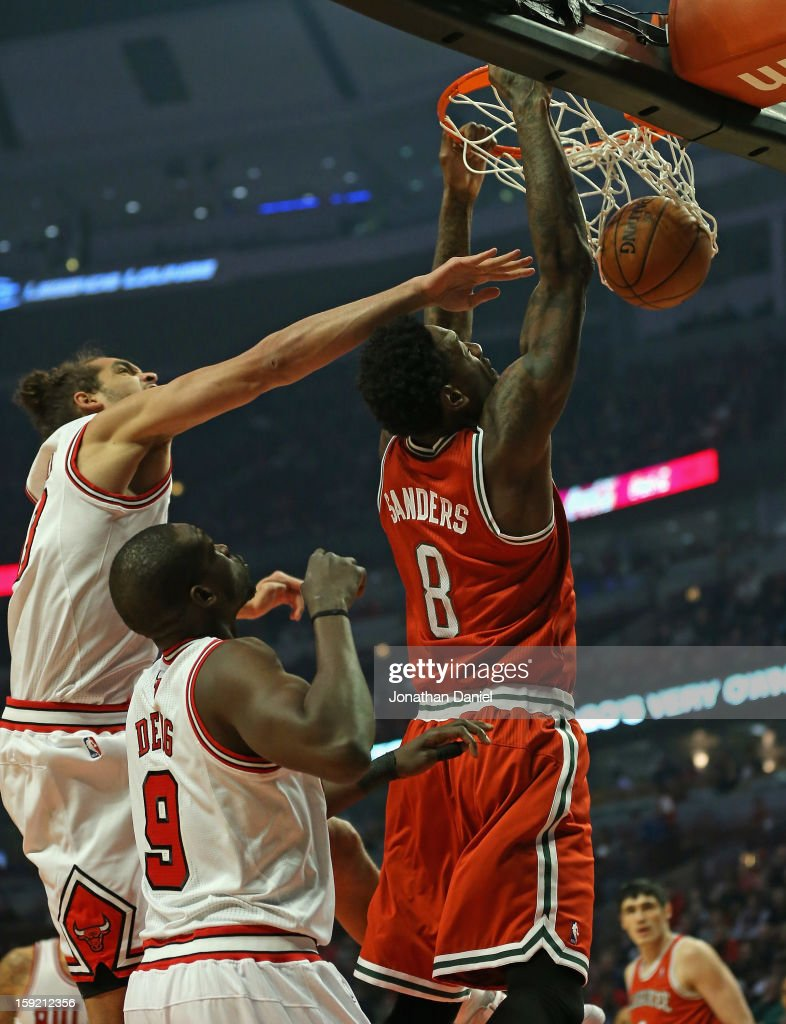 Larry Sanders #8 of the Milwaukee Bucks dunks the ball under pressure from Loul Deng #9 and Joakim Noah #13 of the Chicago Bulls at the United Center on January 9, 2013 in Chicago, Illinois.