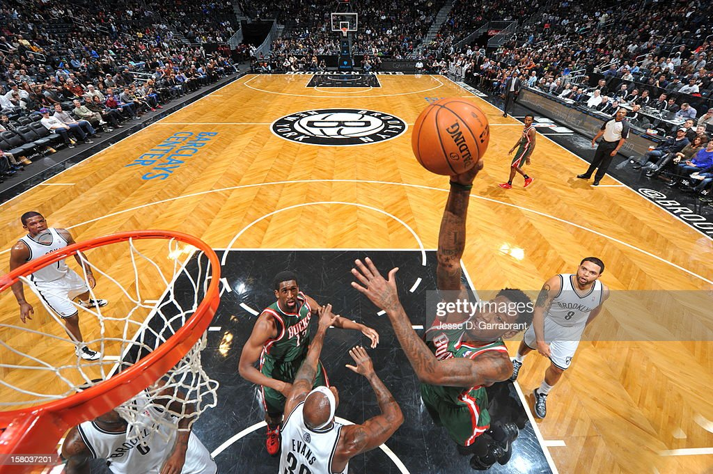 Larry Sanders #8 of the Milwaukee Bucks goes to the basket against Reggie Evans #30 of the Brooklyn Nets during the game at the Barclays Center on December 9, 2012 in Brooklyn, New York.