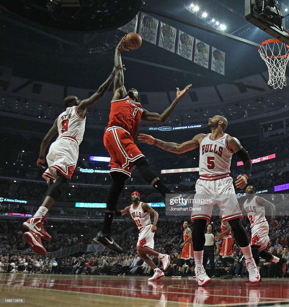 Larry Sanders #8 of the Milwaukee Bucks leaps for a rebound between Loul Deng #9 (L) and Carlos Boozer #5 of the Chicago Bulls at the United Center on January 9, 2013 in Chicago, Illinois.