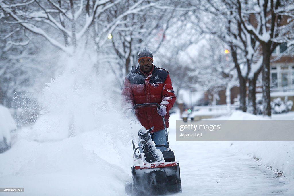 Larry Thomas snow blows several inches of snow from a sidewalk as the area deals with record breaking freezing weather January 6, 2014 in Detroit, Michigan. Michigan and most of the Midwest received their first major snow storm of 2014 last week and subzero temperatures are expected most of this week with wind-chill driving temperatures down to 50-70 degrees below zero. A 'polar vortex' weather pattern is bringing some of the coldest weather the U.S. has had in almost 20 years.