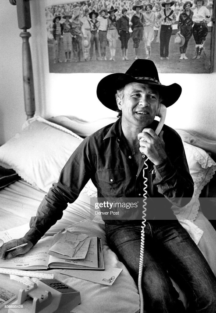 Larry uses the bedroom and bed as his office and desk in their small cabin at the ranch which is being remodeled. and added on to. Here he conducts business on the phone. In background is an old hand colored photo of rodeo cowgirls which hangs above the bed. The cabin has several old photos from rodeos on wall. Credit: The Denver Post
