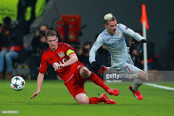 Lars Bender of Bayer Leverkusen tackles Antoine Griezmann of Atletico Madrid during the UEFA Champions League round of 16 match between Bayer 04...