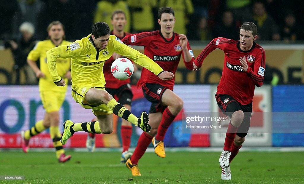 Lars Bender (R) of Leverkusen and Robert Lewandowski (L) of Dortmund battle for the ball during the Bundesliga match between Bayer 04 Leverkusen and Borussia Dortmund at BayArena on February 3, 2013 in Leverkusen, Germany.