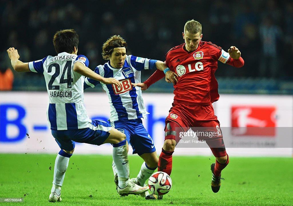Lars Bender of Leverkusen is challenged by Hajime Hosogai and Genki Haraguchi of Berlin during the Bundesliga match between Hertha BSC and Bayer 04...