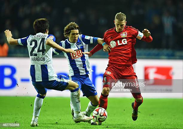 Lars Bender of Leverkusen is challenged by Hajime Hosogai and Genki Haraguchi of Berlin during the Bundesliga match between Hertha BSC and Bayer 04...