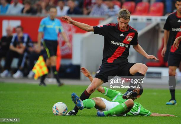 Lars Bender of Leverkusen is challenged by Makoto Hasebe of Wolfsburg during the Bundesliga match between Bayer 04 Leverkusen and VfL Wolfsburg at...