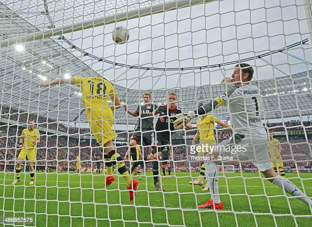 Lars Bender of Leverkusen scores his teams first goal against goalkeeper Roman Weidenfeller of Dortmund during the Bundesliga match between Bayer...