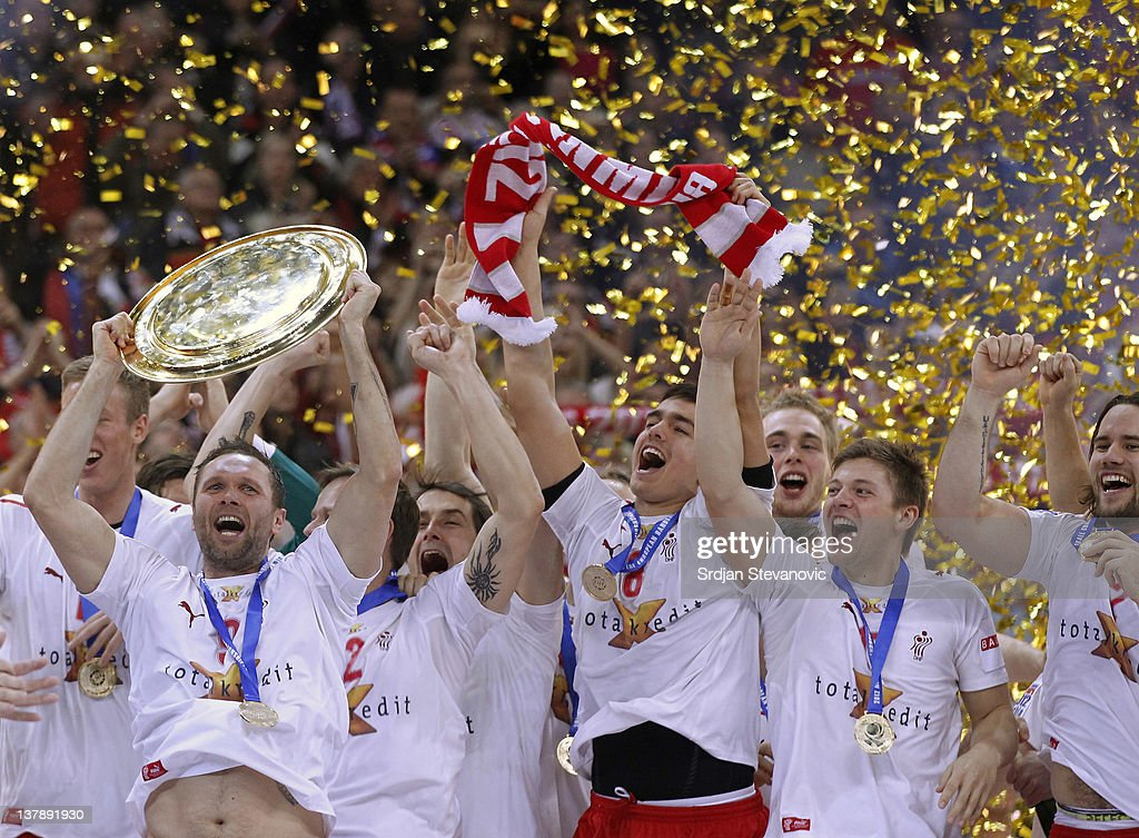 Lars Christiansen of Denmark (L) lifts the winning trophy to his team on the podium after winning 21-19 the Men's European Handball Championship final match between Serbia and Denmark at Beogradska Arena on January 29, 2012 in Belgrade, Serbia. (Photo by Srdjan Stevanovic/Getty Images