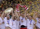 Lars Christiansen of Denmark lifts the winning trophy to his team on the podium after winning 2119 the Men's European Handball Championship final...